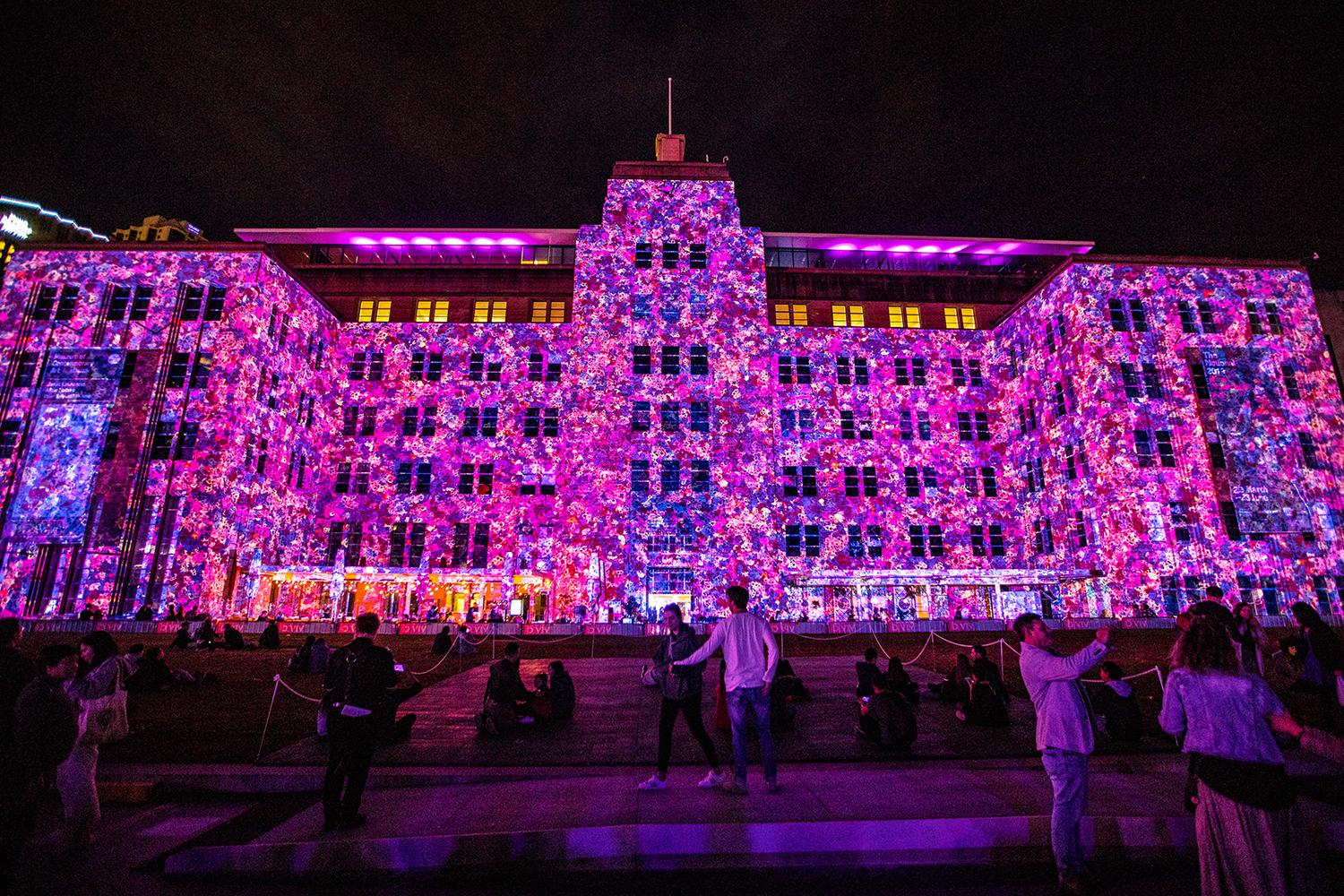 Crowds enjoying the Let Me Down light projection on the Museum of Contemporary Art (MCA) Australia building in The Rocks during Vivid Sydney 2019